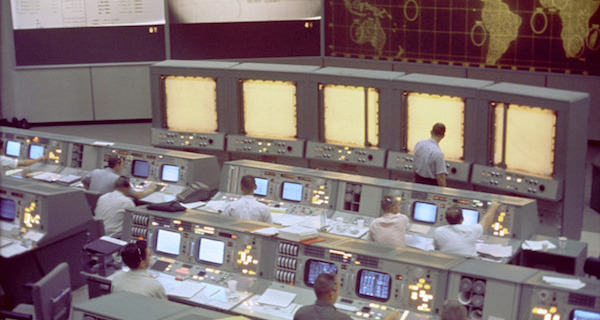 Overall view of the Mission Control Center (MCC), Houston, Texas, during the Gemini 5 flight. Note the screen at the front of the MCC which is used to track the progress of the Gemini spacecraft.